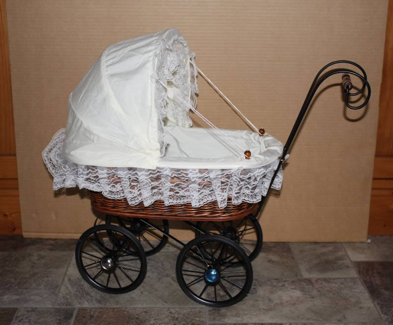 Small brown cane pram with white hood