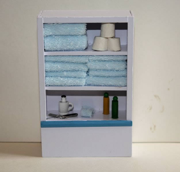 White bathroom shelves with towels and acces.