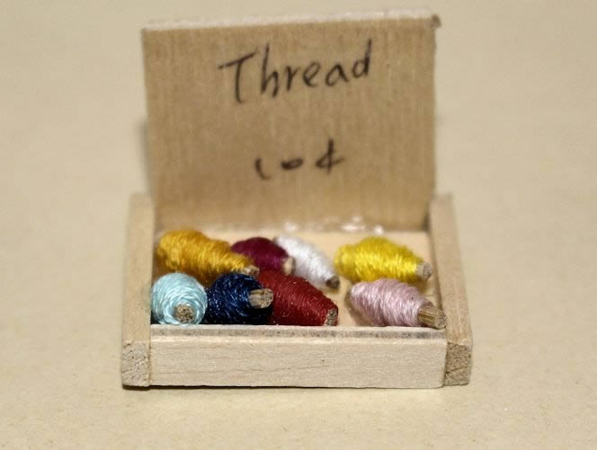 Wooden box of coloured threads