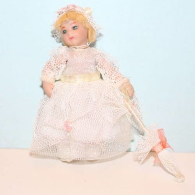 Porcelain doll in white net dress and parasol